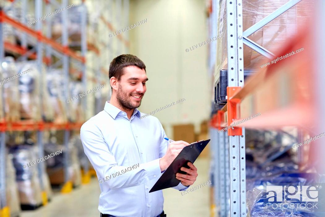 Stock Photo: wholesale, logistic, business, export and people concept - happy man or manager with clipboard checking goods at warehouse.