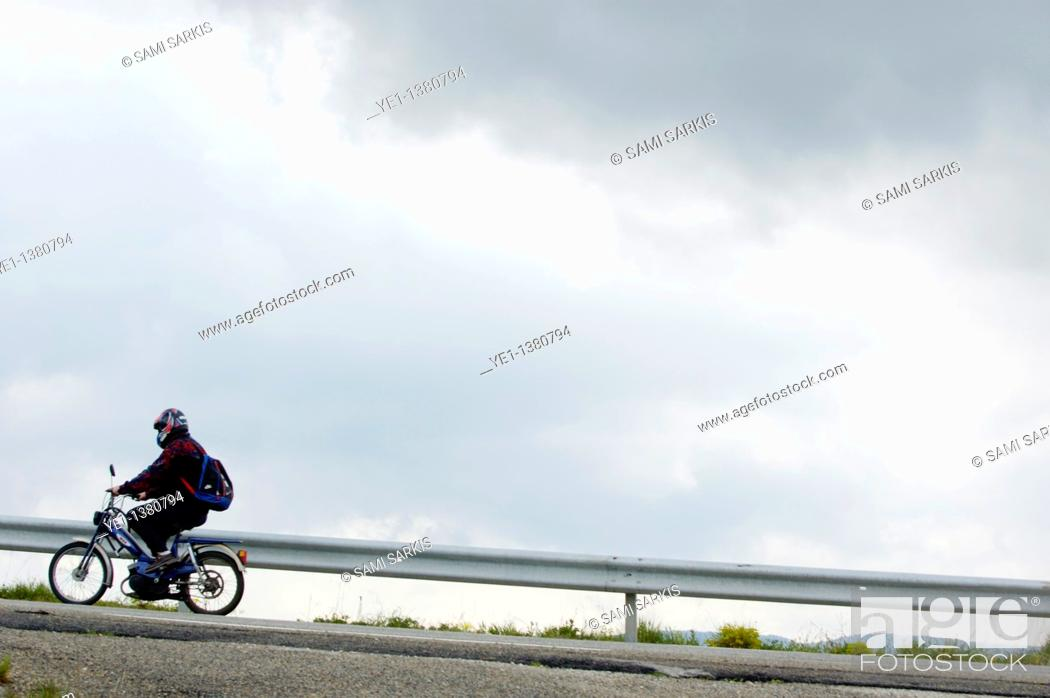 Stock Photo: Moped on a road against a stormy sky, Saint-Paul-Trois-Châteaux, Drome, France.
