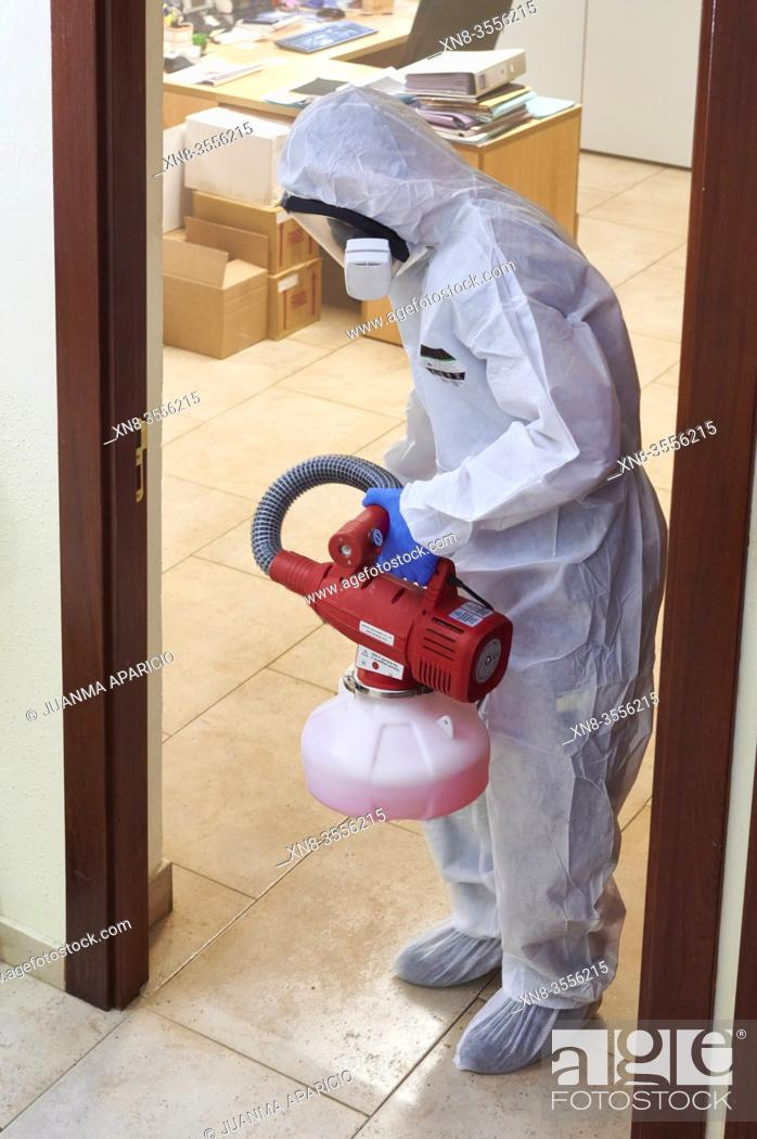 Imagen: Worker in protective suit disinfect interior office.