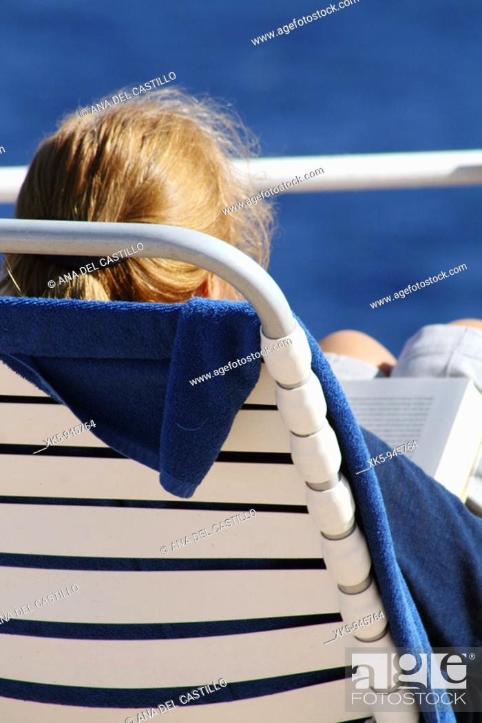 Stock Photo: A woman reading on the deck of a cruise ship around the Atlantic ocean.