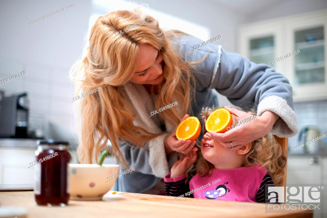Stock Photo: Young girl sitting at kitchen table, mother holding halved orange in front of daughter's eyes.