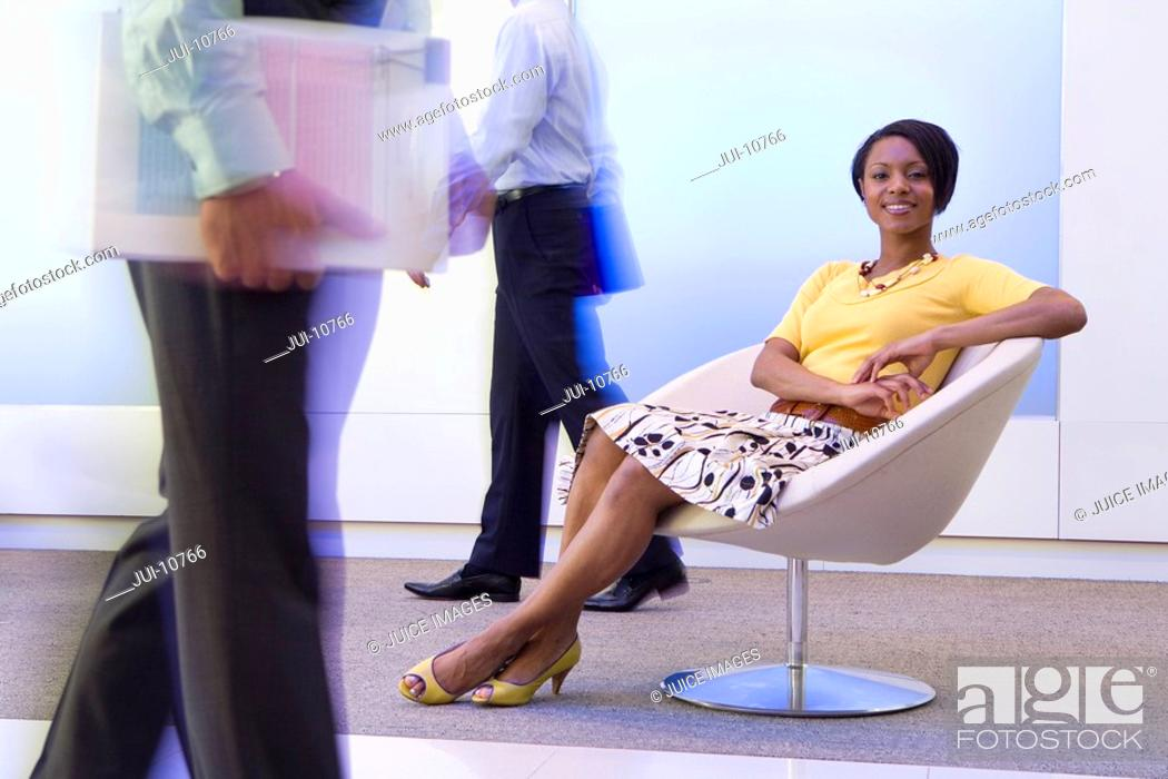 Stock Photo: 20's African American businesswoman sitting in chair in office with male colleagues walking by in foreground and background,.
