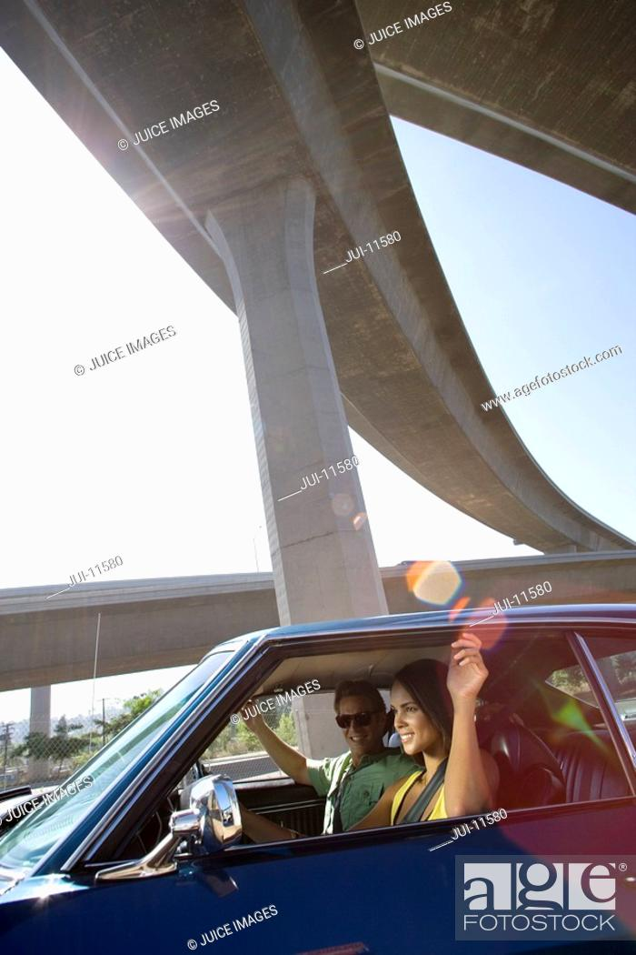 Stock Photo: Young couple in car beneath overpass, smiling lens flare.