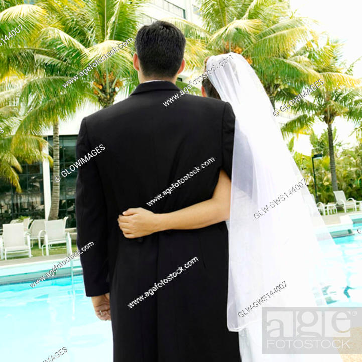 Stock Photo: Rear view of a newlywed couple standing at the poolside.