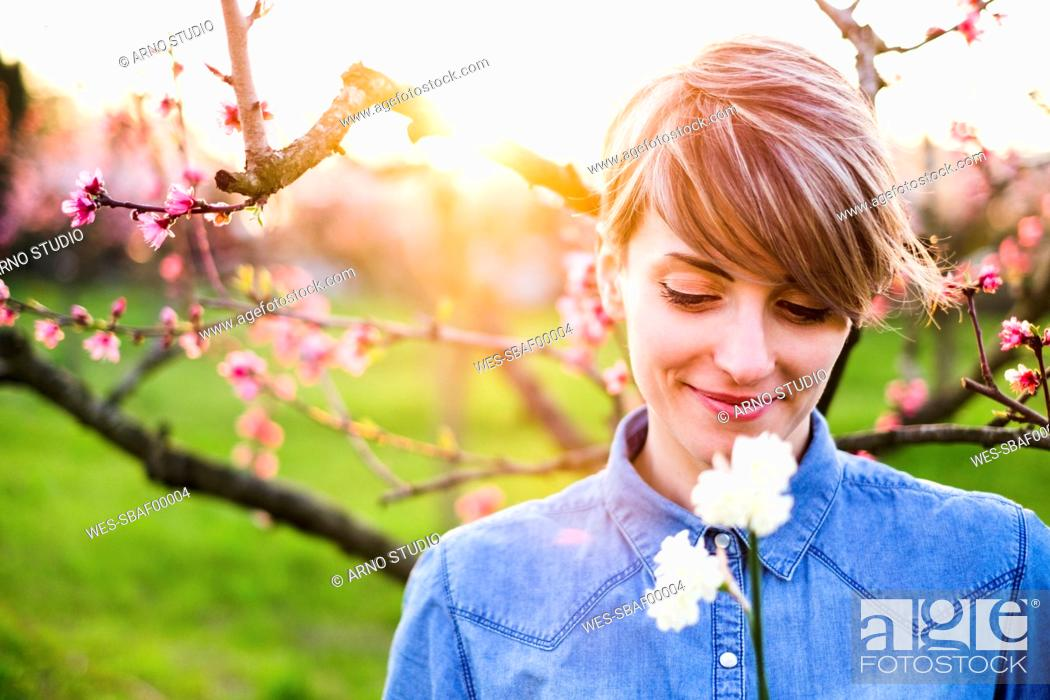 Stock Photo: Close-up of smiling woman looking at flowers in park during sunset.