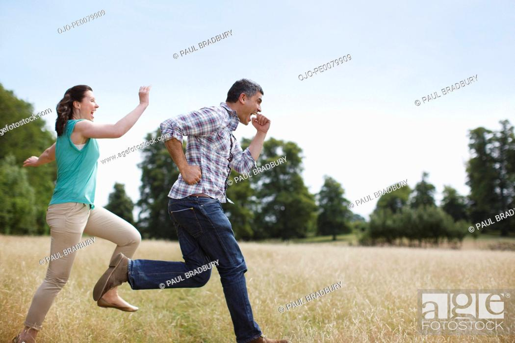 Stock Photo: Playful couple running in rural field.