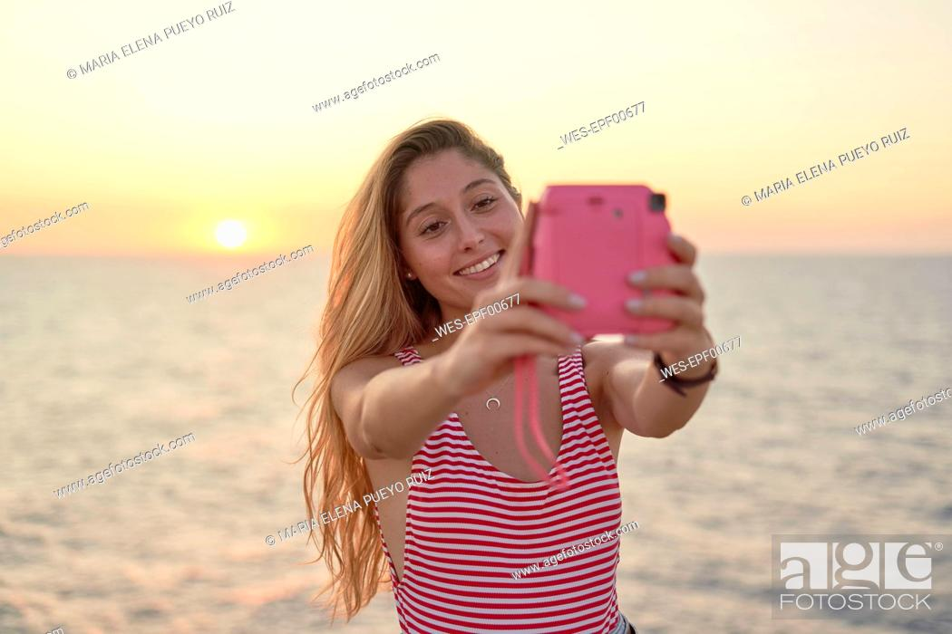 Stock Photo: Young woman taking pictures of herself at sunset by the sea.