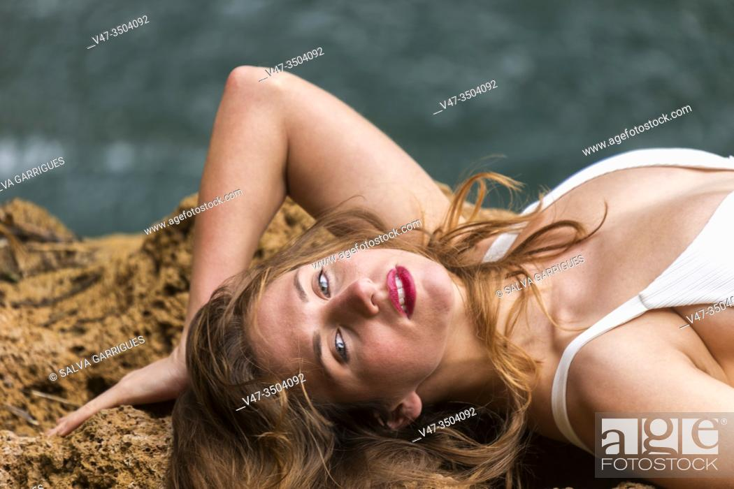 Photo de stock: Woman lying on the rock by the river wearing a white swimsuit.