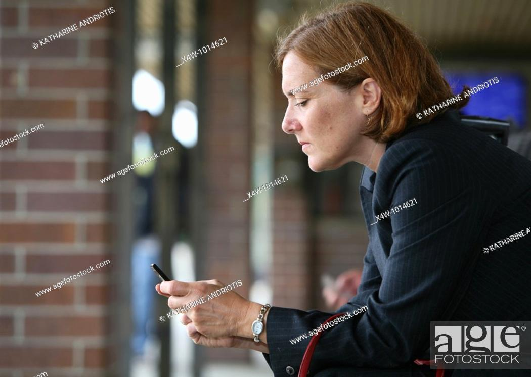 Imagen: Businesswoman texting while waiting for train.