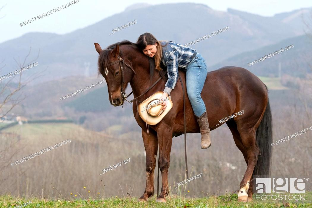 Imagen: A young cowgirl lying on her horse without saddle with a hat in the hand.