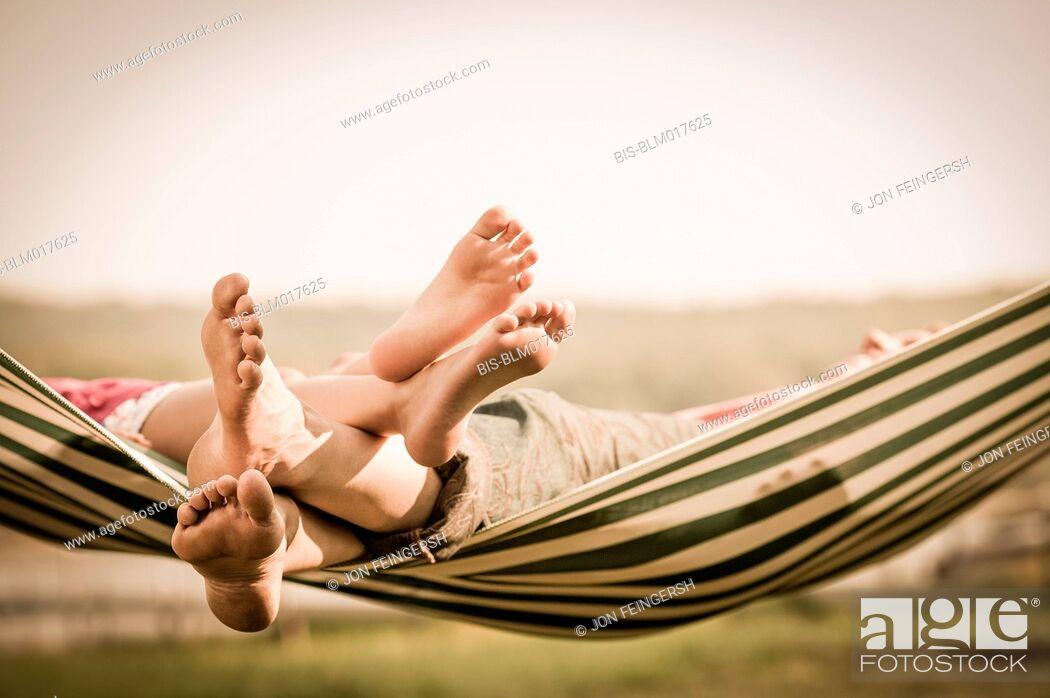 Imagen: Mother and daughter relaxing in hammock outdoors.