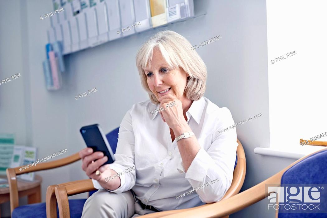 Stock Photo: Mature female patient looking at mobile phone in hospital waiting room.
