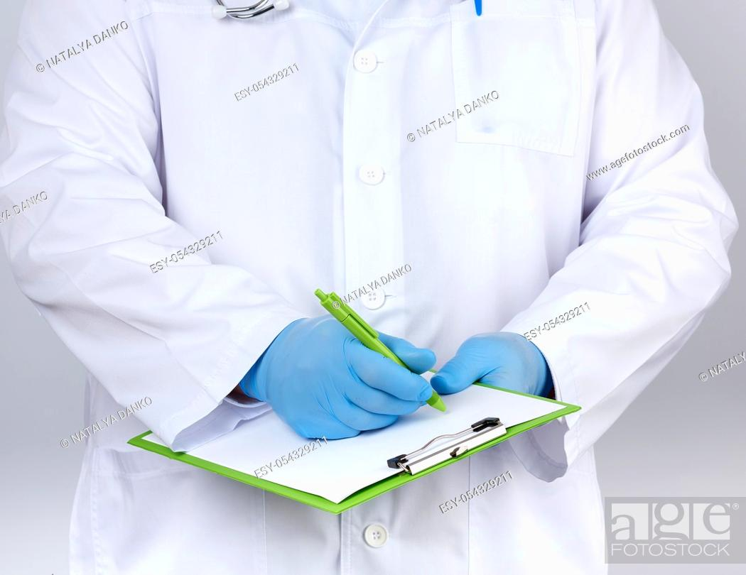 Stock Photo: doctor in a white coat and medical blue gloves records a patientâ. . s medical history, close up.