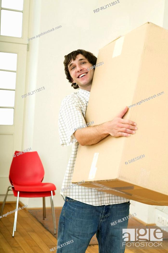 Stock Photo: Young man carrying heavy cardboard box.