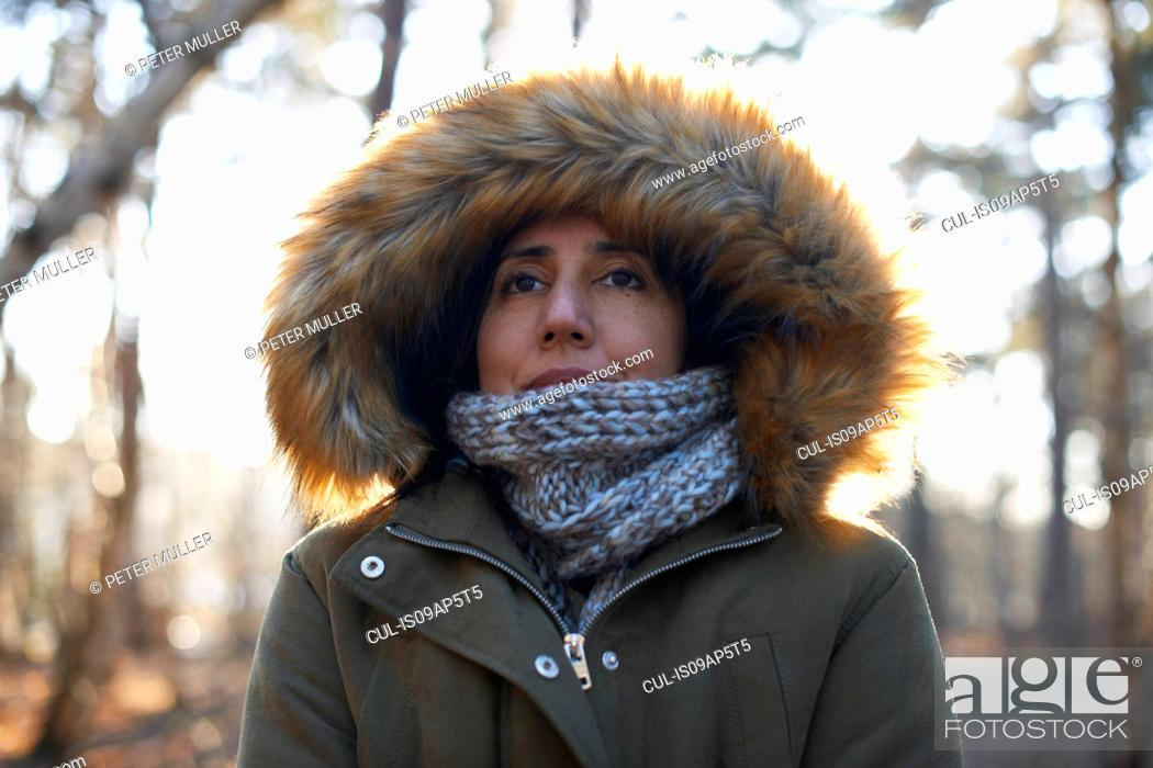 Stock Photo: Portrait of mature woman wearing fur hood and scarf in forest.