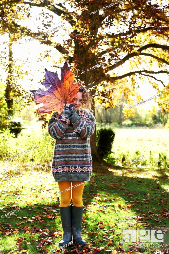 Stock Photo: Girl playing with autumn leaf outdoors.
