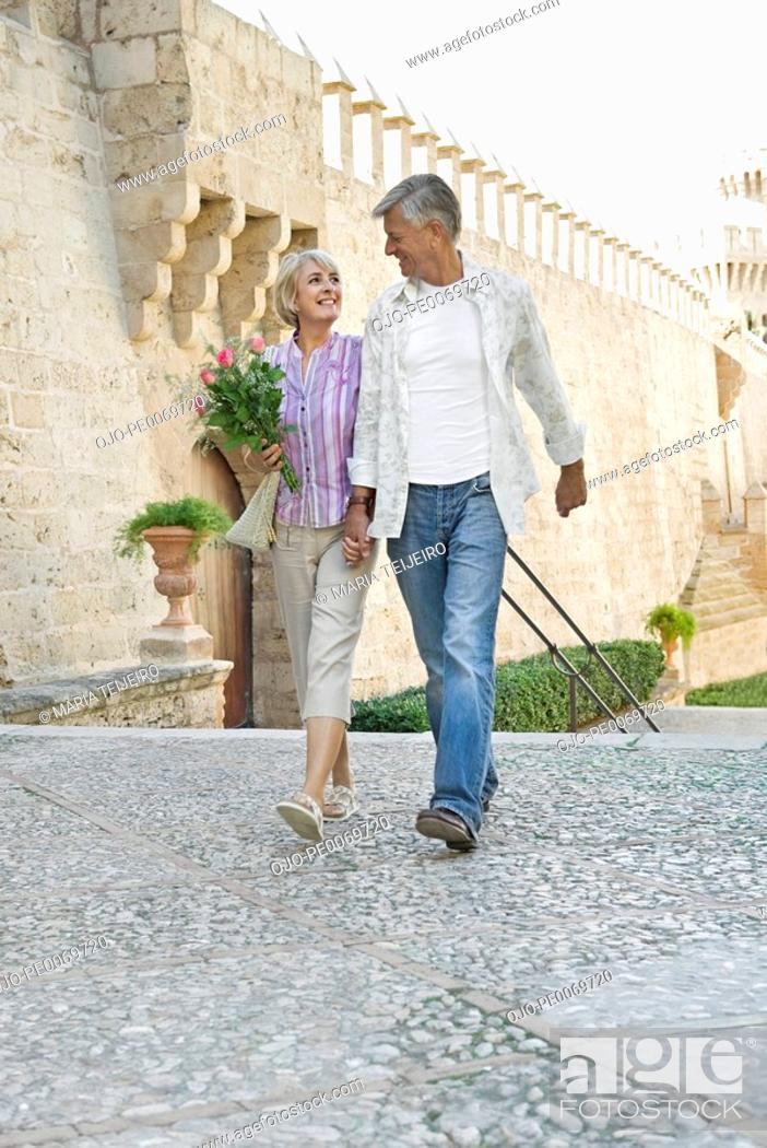 Stock Photo: Man and woman holding hands and walking.