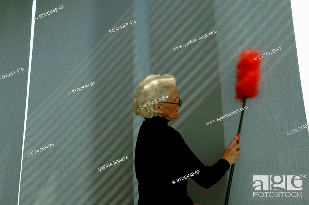 Stock Photo: Senior woman cleaning the wall with a feather duster.