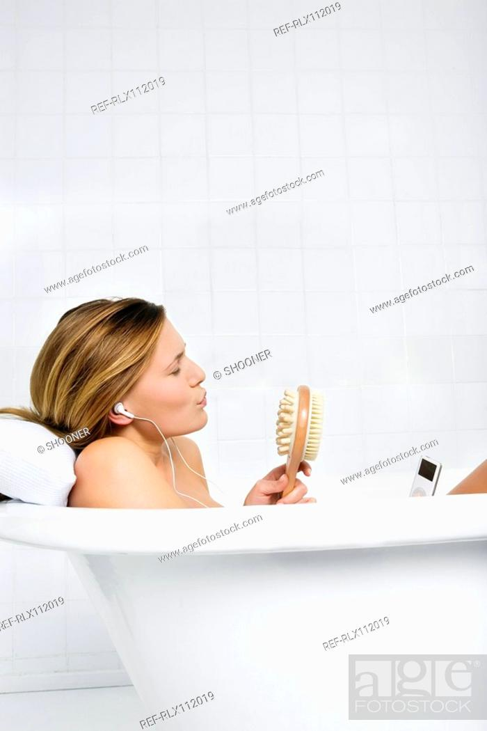Stock Photo: Woman listening to mp3 player in the bath.