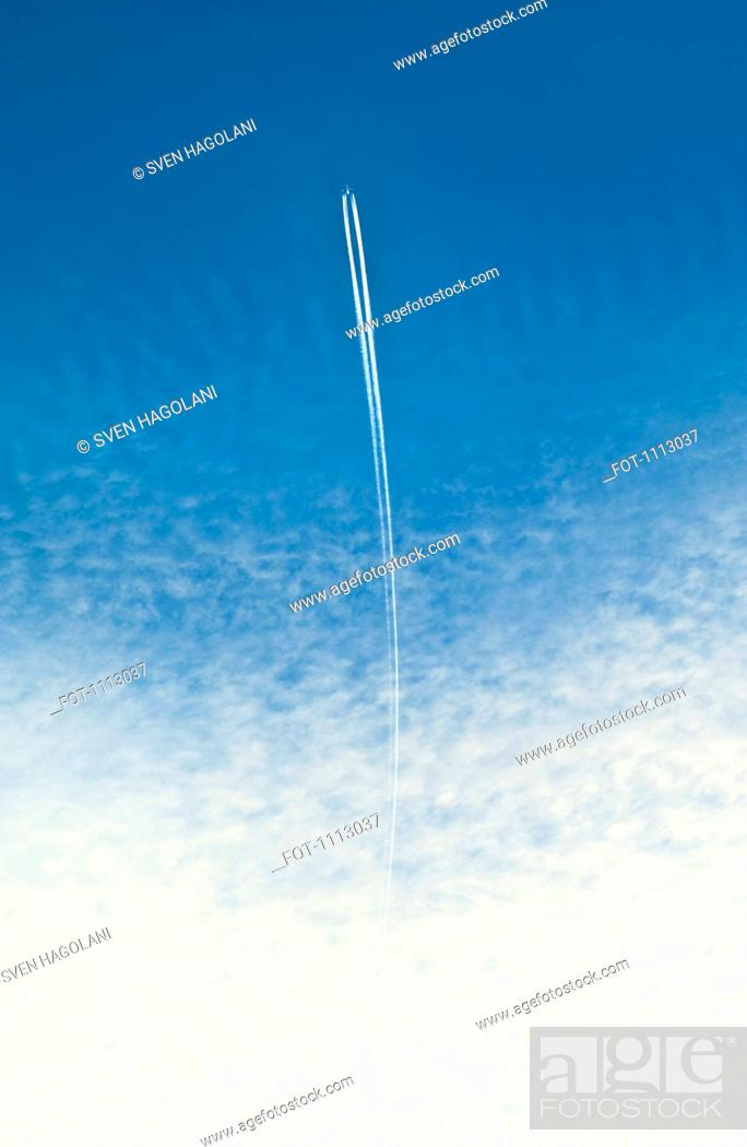 Stock Photo: An airplane with a vapor trail.