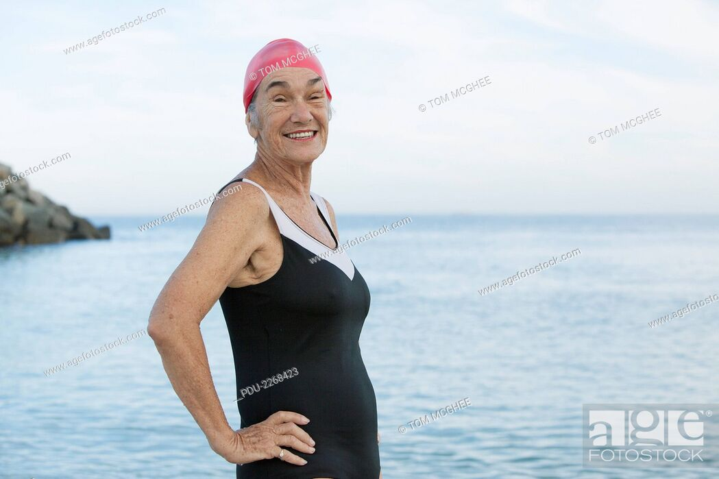 Stock Photo: senior women at beach smiling and posing in black swimsuit and red swim cap.