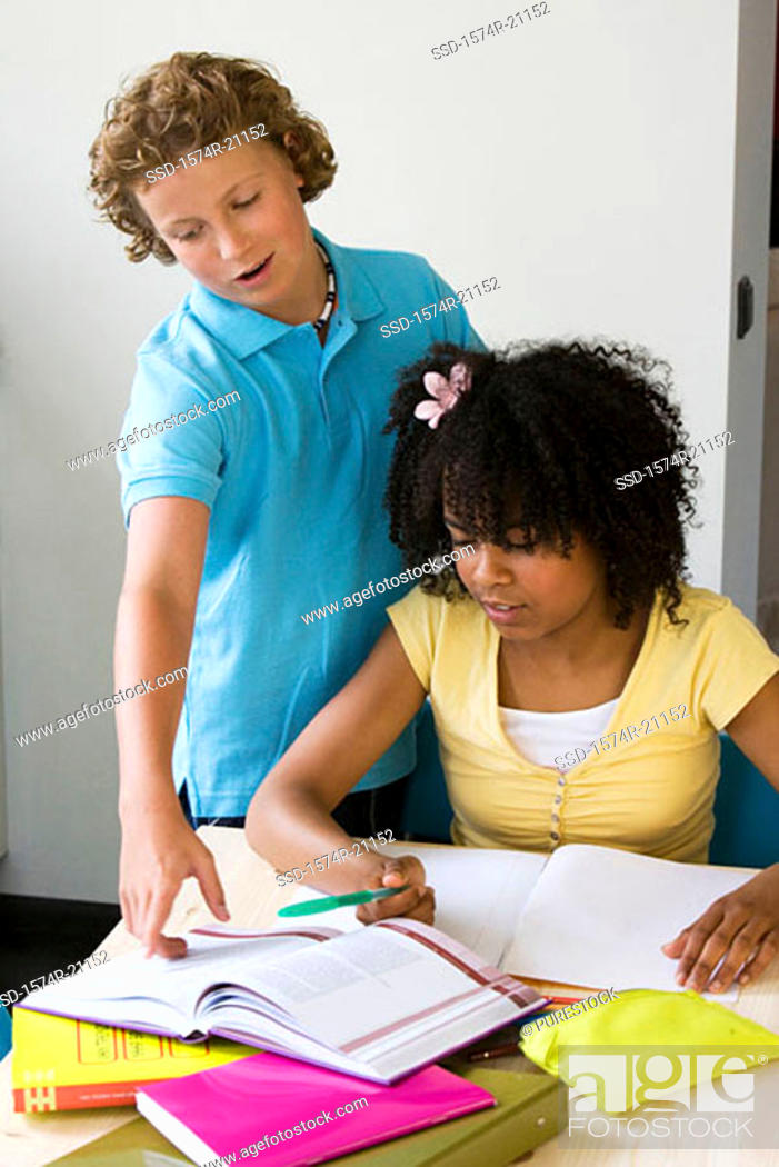 Stock Photo: Girl doing her homework with a boy standing near her.