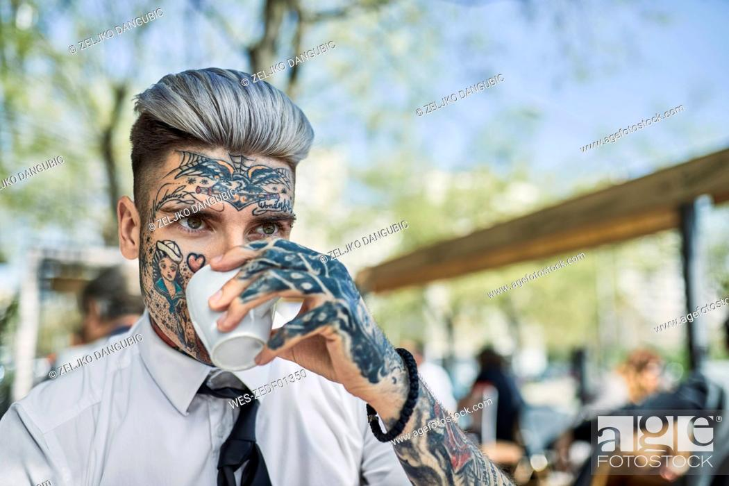 Stock Photo: Young businessman with tattooed face, drinking coffee.