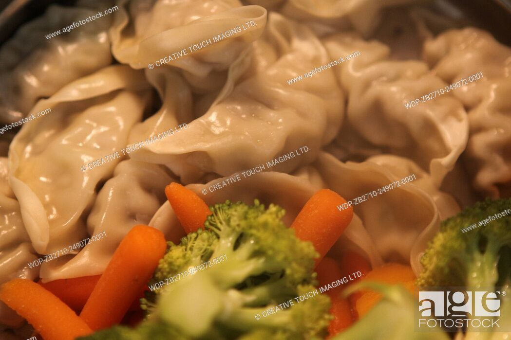 Imagen: Dumplings and vegetables cooking in a steamer.