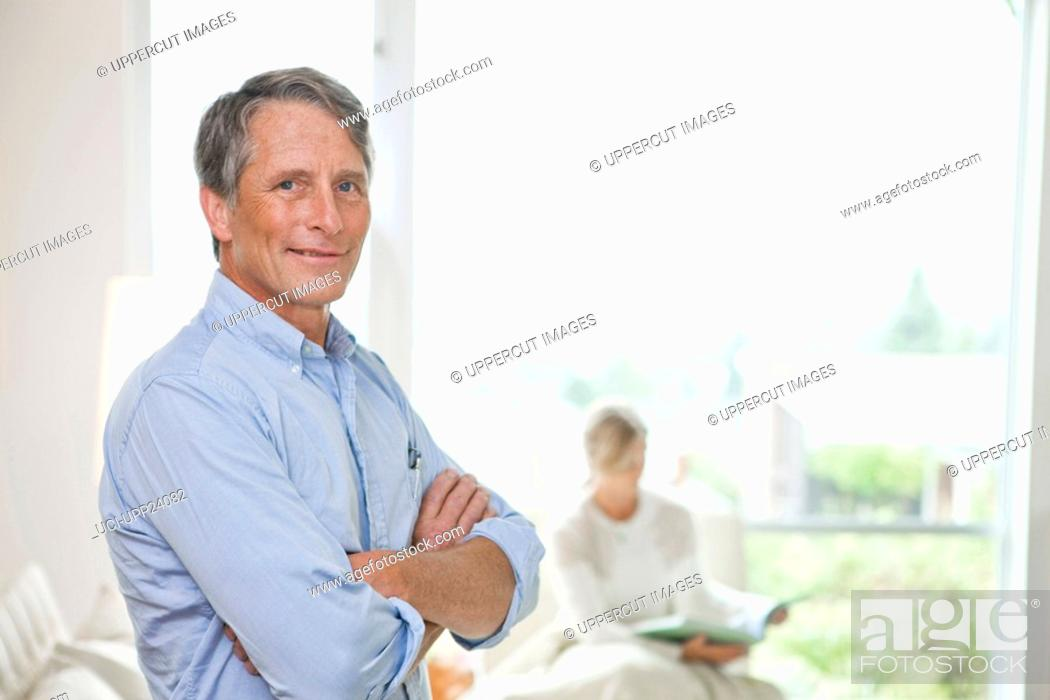 Stock Photo: Portrait of man standing in living room with arms crossed.
