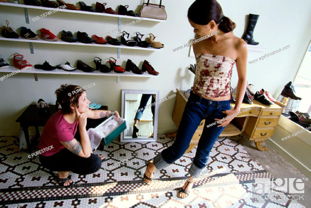 Stock Photo: Young woman trying on sandals in a shoe store.