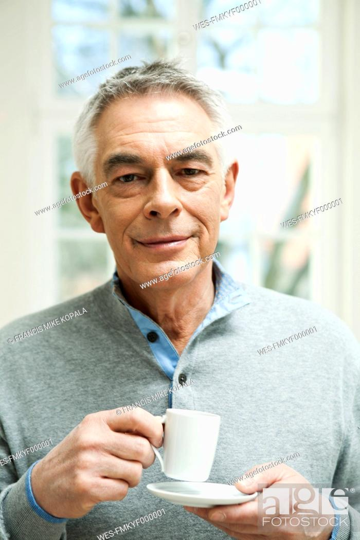 Stock Photo: Germany, Berlin, Senior man with coffee cup, portrait.