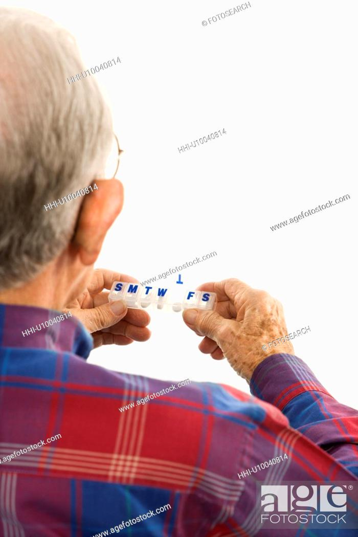 Stock Photo: Back over the shoulder view of Caucasion elderly man holding seven-day pill box with Thursday open.