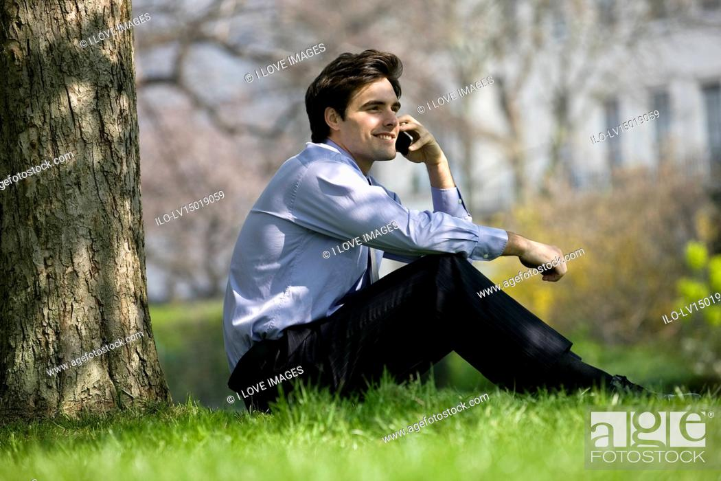 Stock Photo: A businessman sitting on the grass, talking on the phone.