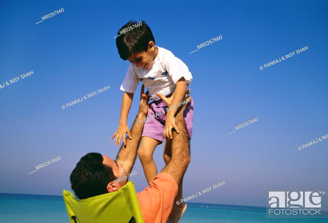 Stock Photo: A father hoisting his son near the vast sea.