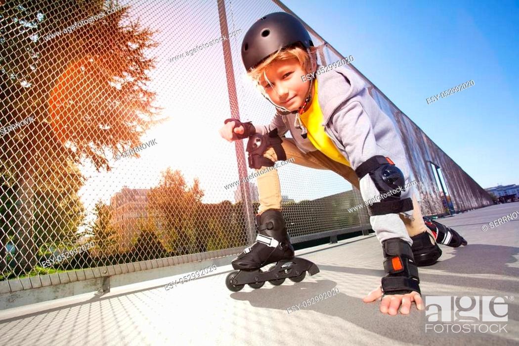 Stock Photo: Close-up portrait of preteen boy, roller skater in protective gear, posing on floor at outdoor rollerdrom.