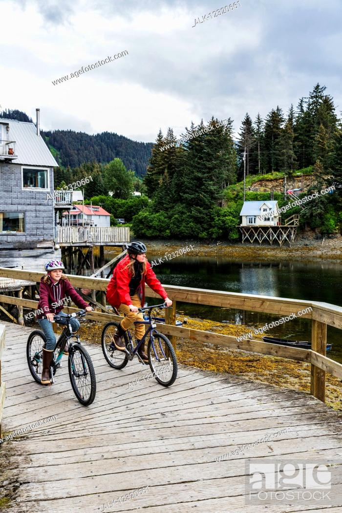 Imagen: Mother and daughter bicycling on the historic oceanside boardwalk, Seldovia, Southcentral Alaska, USA.
