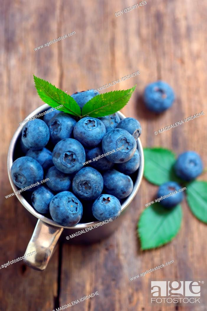 Stock Photo: Blueberries in a cup on a wooden table.