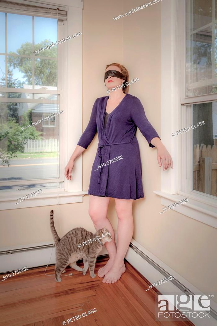 Stock Photo: Young blindfolded woman and her cat in the living room.