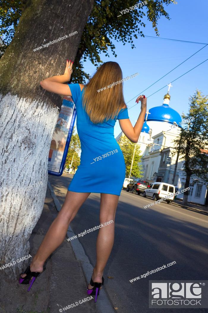 Imagen: Beautiful, attractive Ukrainian woman wearing a blue dress lying on a tree and calling a taxi near the Orthodox Cathedral of St Michael to a photographic.