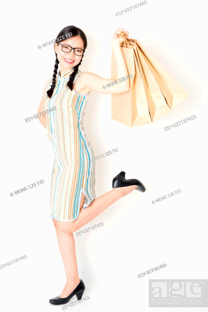 Stock Photo: Portrait of young Asian girl in traditional cheongsam dress shopping, hand holding paper bag, celebrating Chinese Lunar New Year or spring festival.
