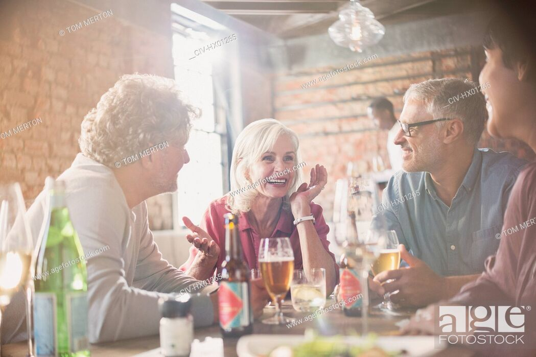 Photo de stock: Couples talking and drinking beer at restaurant table.