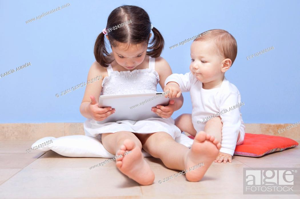 Stock Photo: Baby boy discovering with her sister a tablet pc.