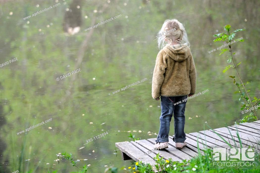 Stock Photo: Four year old girl standing on her own by the side of a pond.