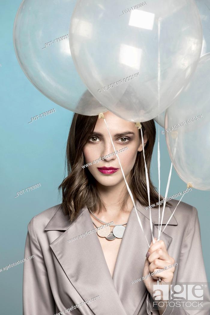 Imagen: Portrait of female fashion model holding balloons.