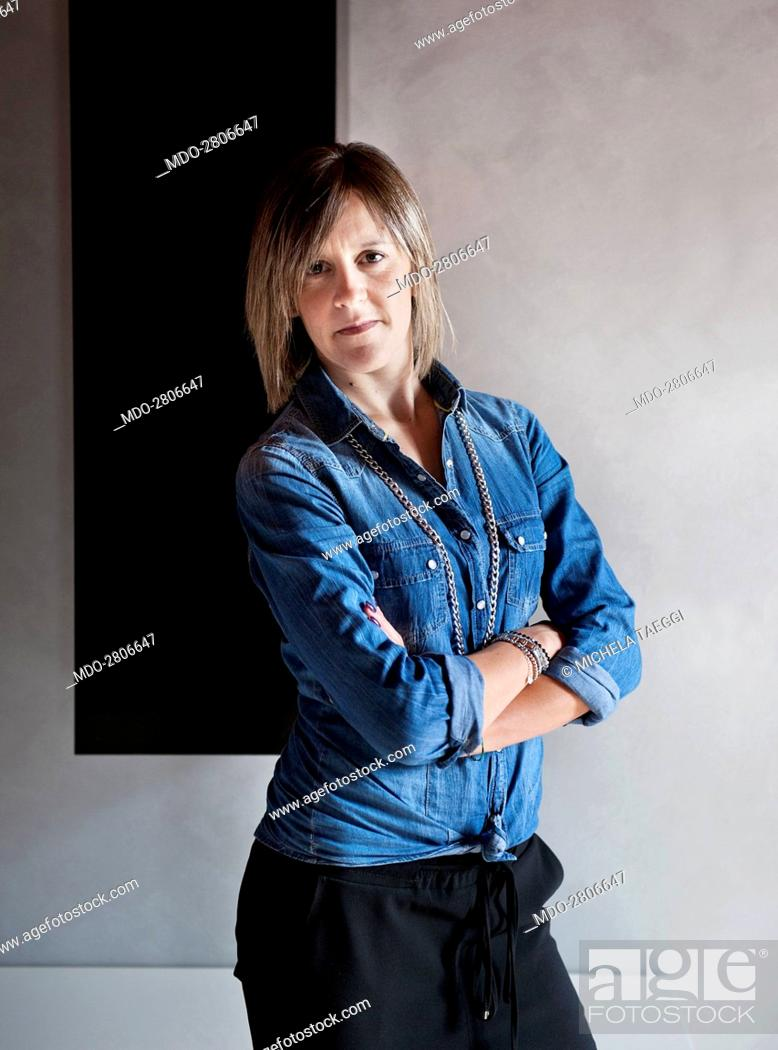 Stock Photo: A woman posing with folded arms for the photocall. Caprino Bergamasco (Italy), 15th October 2014.