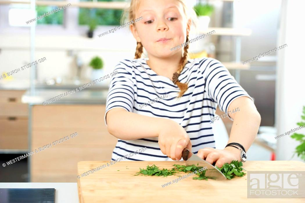 Stock Photo: Girl cuts fresh parsley.