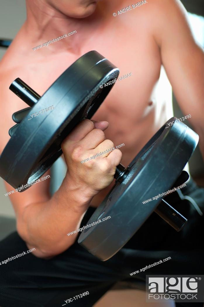 Stock Photo: Midsection of young man curling dumbbell at a gym.