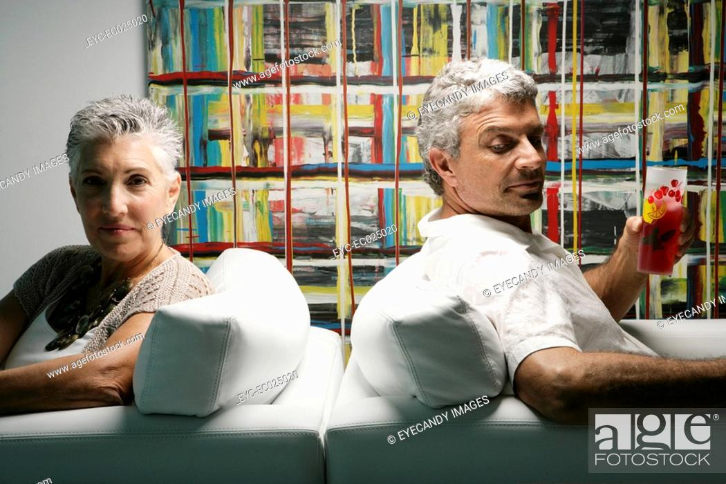 Stock Photo: Two mature people sitting back to back.