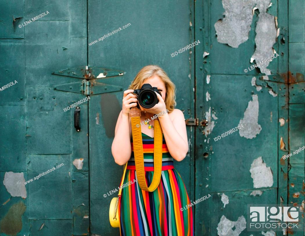 Stock Photo: Young woman in striped dress in front of industrial door taking photographs, portrait.