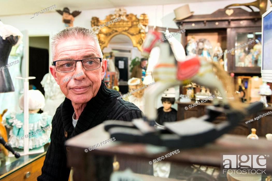 Stock Photo: Tilburg, Netherlands. Mature adult vintage shop owner selling retro interior decoration items from his down town store.